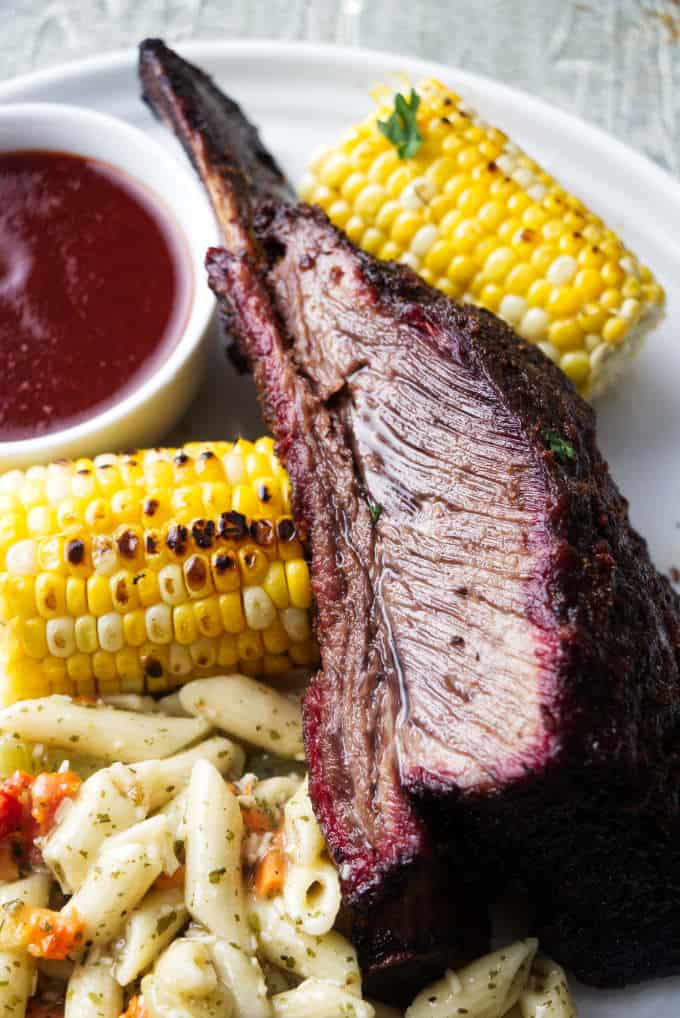 A Dino beef rib on a plate with corn and pasta salad.