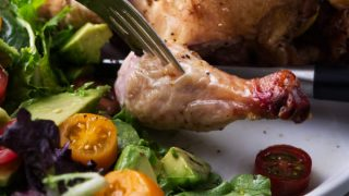 A smoked Cornish game hen on a plate with salad.