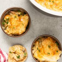 Overhead of ninja foodi turkey pot pie dished into bowls with wooden spoon