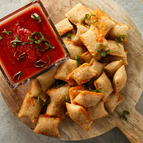 Overhead of pizza rolls stacked on wood cutting board with pizza sauce for dipping.