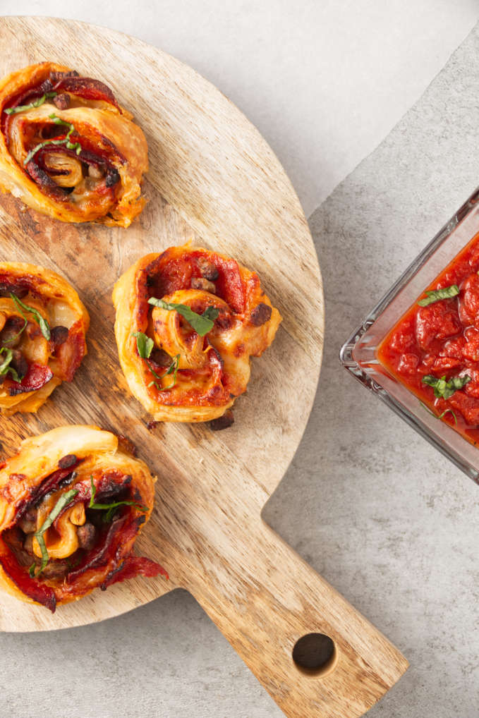 Crispy air fryer pizza rolls on cutting board with pizza sauce in bowl for dipping.