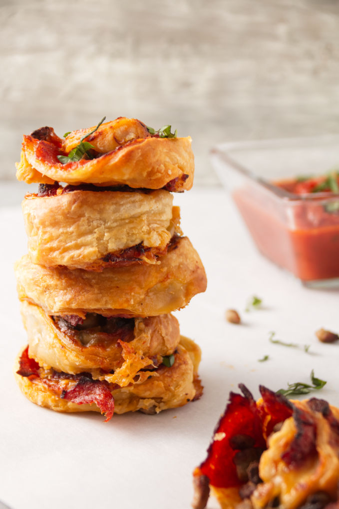 Crispy air fryer pizza rolls in a stack with pizza sauce for dipping.