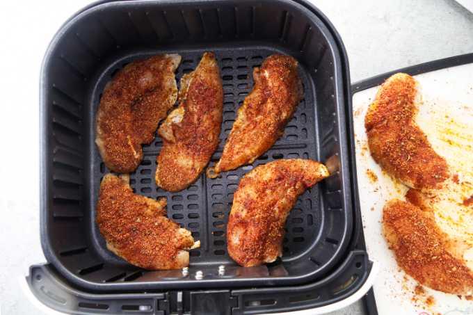 Placing chicken tenders in an air fryer.