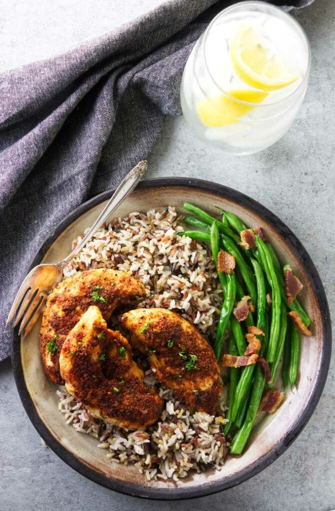 A serving of chicken tenders on a plate with rice and green beans.