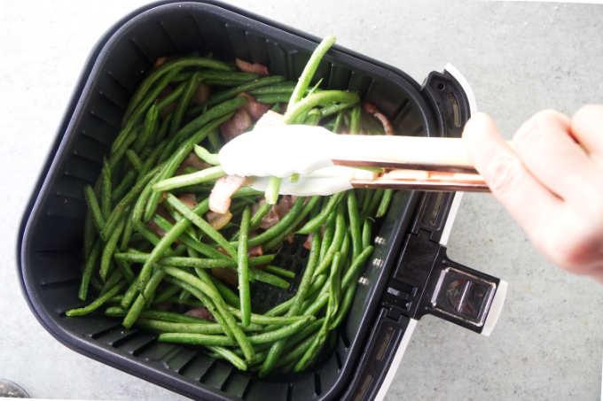 Stirring green beans in an air fryer.