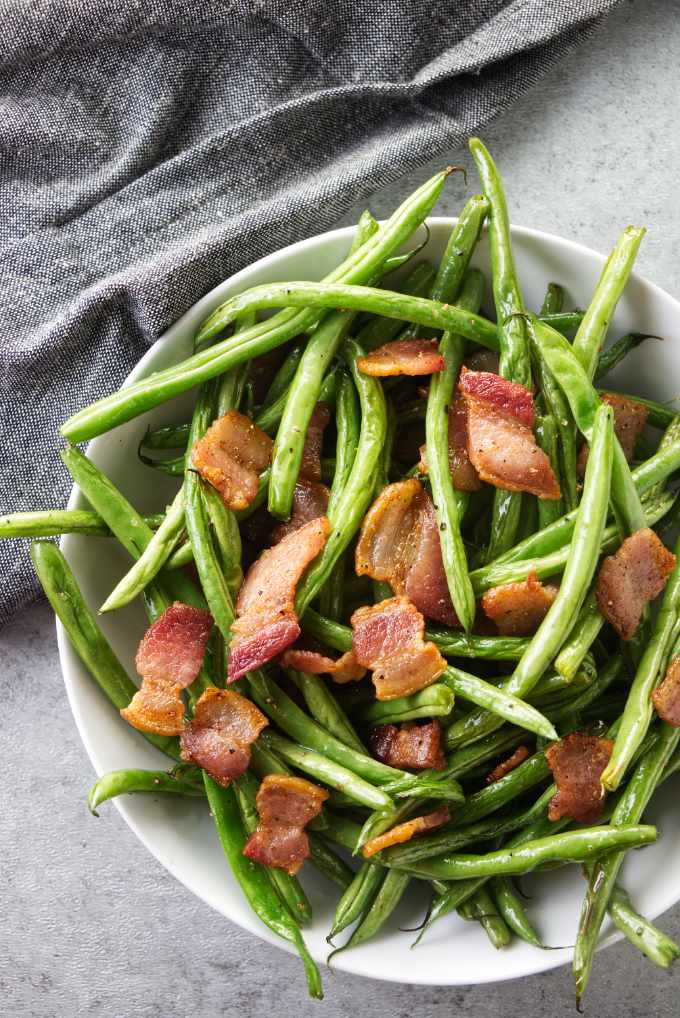 A bowl of green beans with bacon.