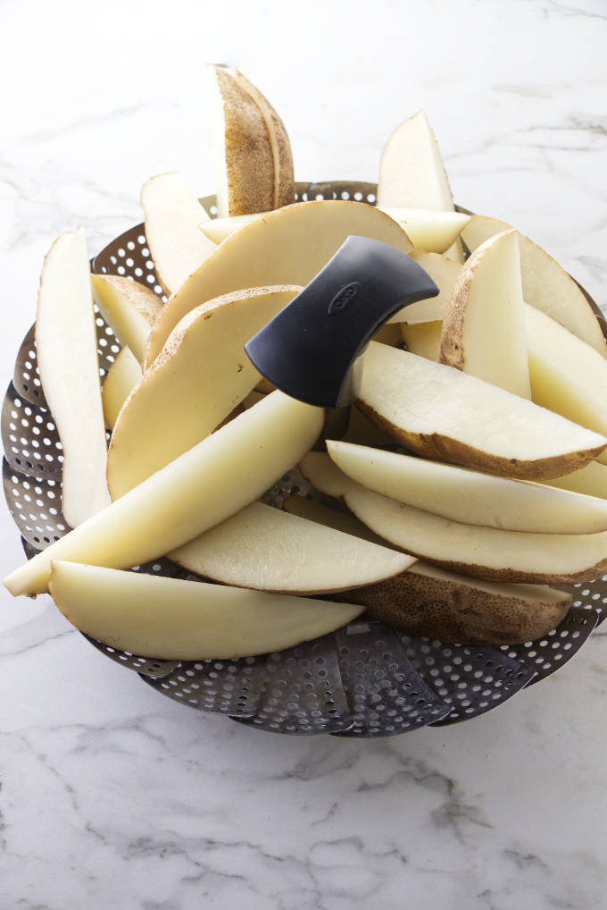 Placing potato wedges in a steamer basket.