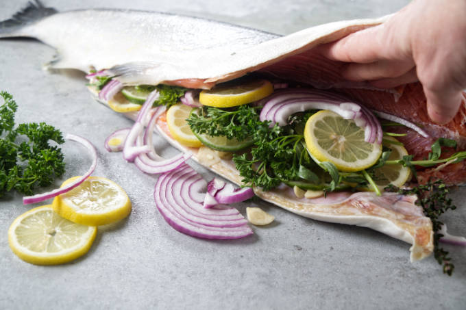 Stuffing a whole salmon with lemon, onion, garlic, and herbs.