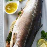 Whole salmon stuffed with citrus and aromatics on serving platter