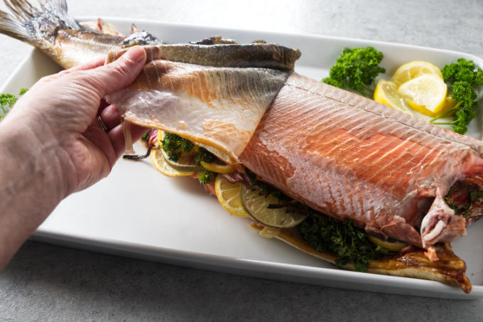 Removing the skin from a cooked salmon.
