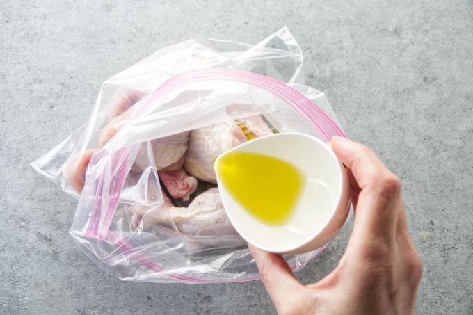 Adding olive oil to chicken legs.