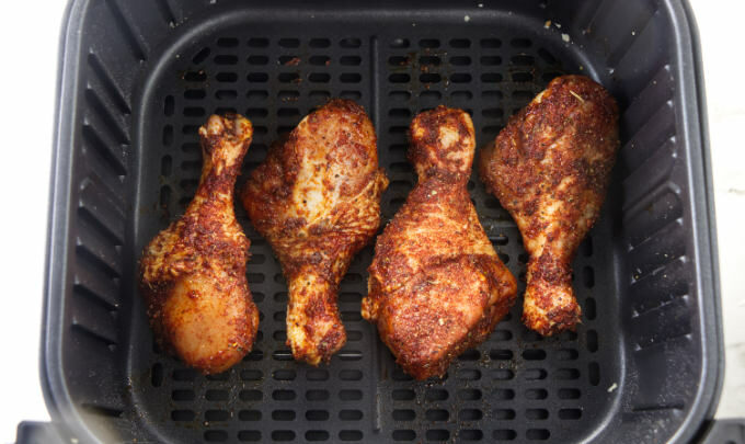Chicken legs coated in dry rub and placed in an air fryer basket.