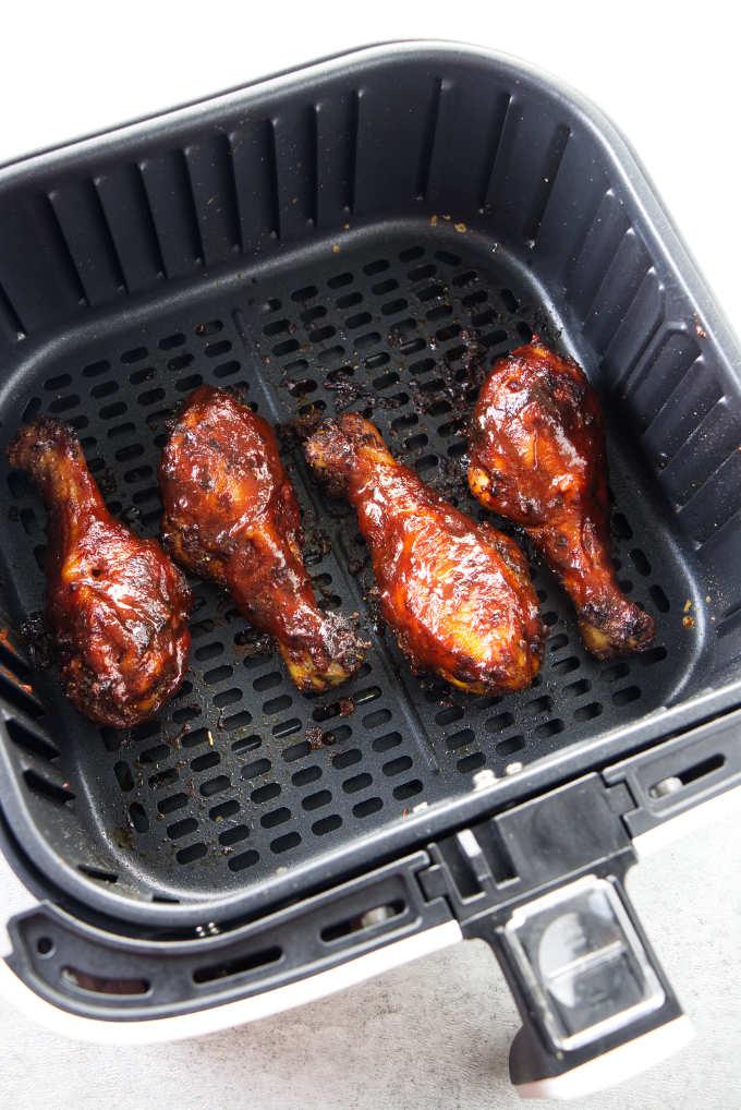 BBQ chicken legs in an air fryer basket.