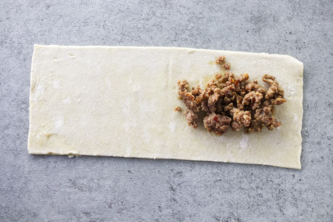 Sausage on half of a strip of puff pastry.