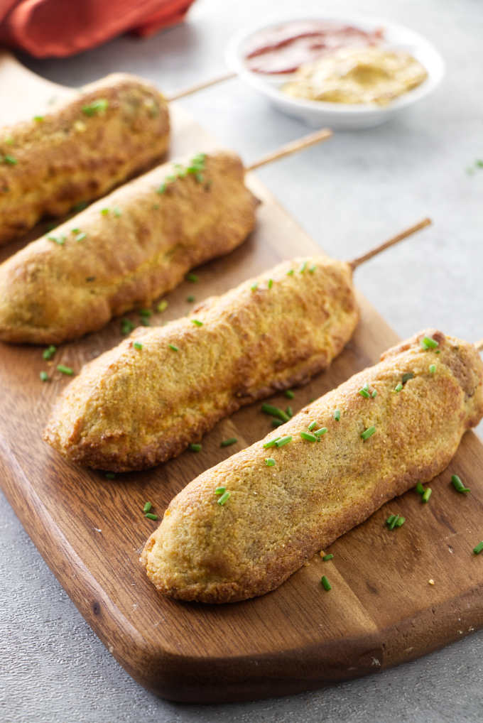 Homemade corn dogs on a serving board with ketchup and mustard in the background.